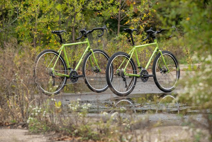 Two Surly Disc Trucker bikes in Pea Lime Soup color side by side with one slighty ahead on wet muddy trail in a prairie