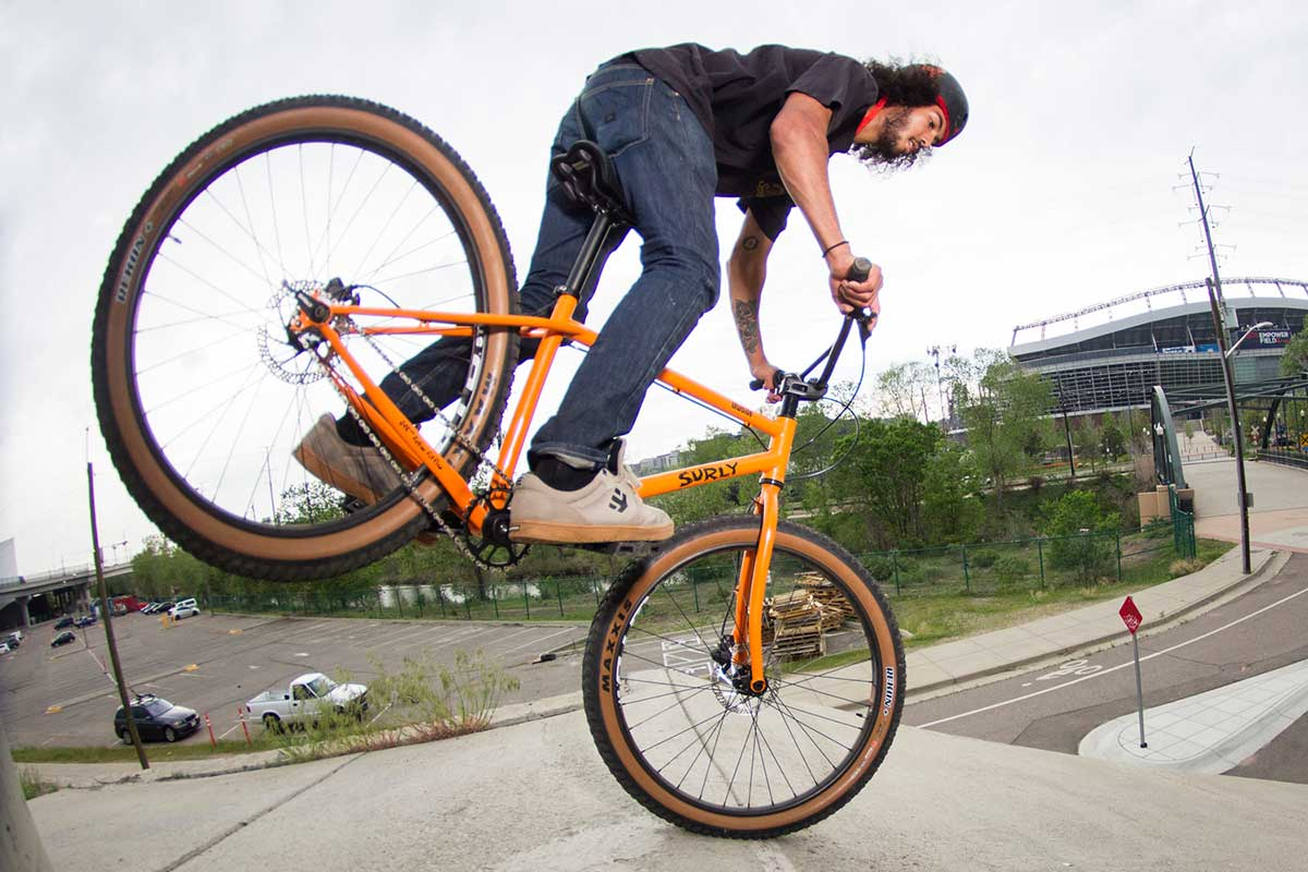 Biker with helmet riding with Surly Lowside and balancing on front wheel only