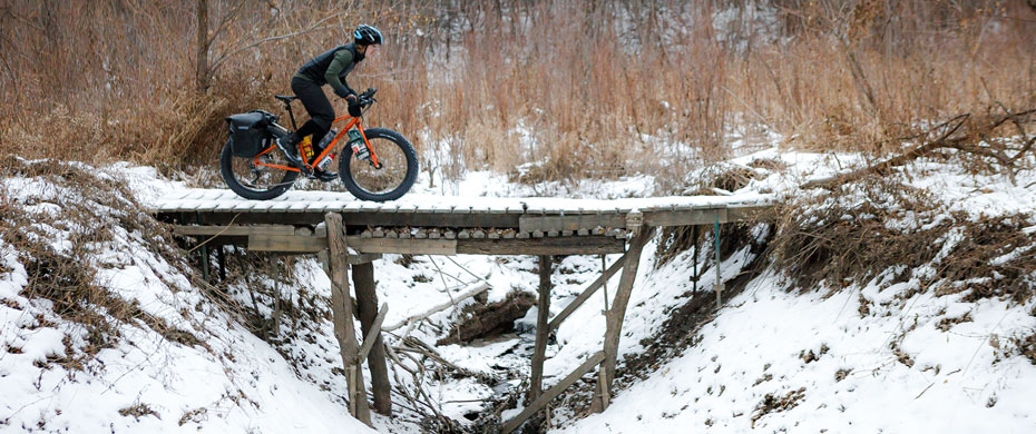 Pugsley riding over a wooden bridge