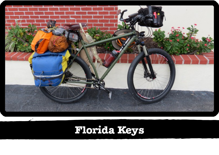 Right side view of a Surly bike, green, loaded with gear, in front of a red brick wall - Florida Keys tag below image