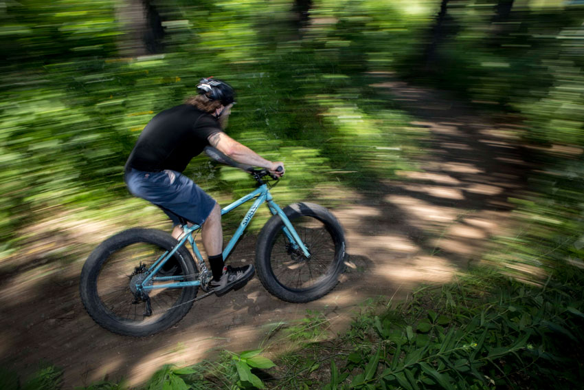 Right side blurred view of a cyclist, on a light blue Surly Wednesday fat bike, riding on a dirt trail in the woods