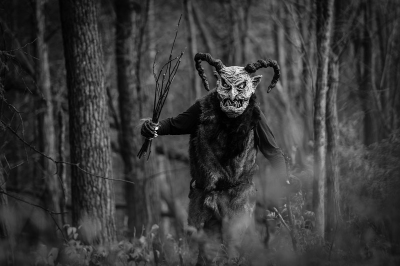 Front view of a person in a Krampus costume in the forest - black and white image