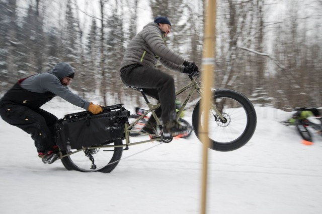 Right side view of a cyclist, riding a Surly Big Fat Dummy bike in the snow, popping a wheelie with a person on the back