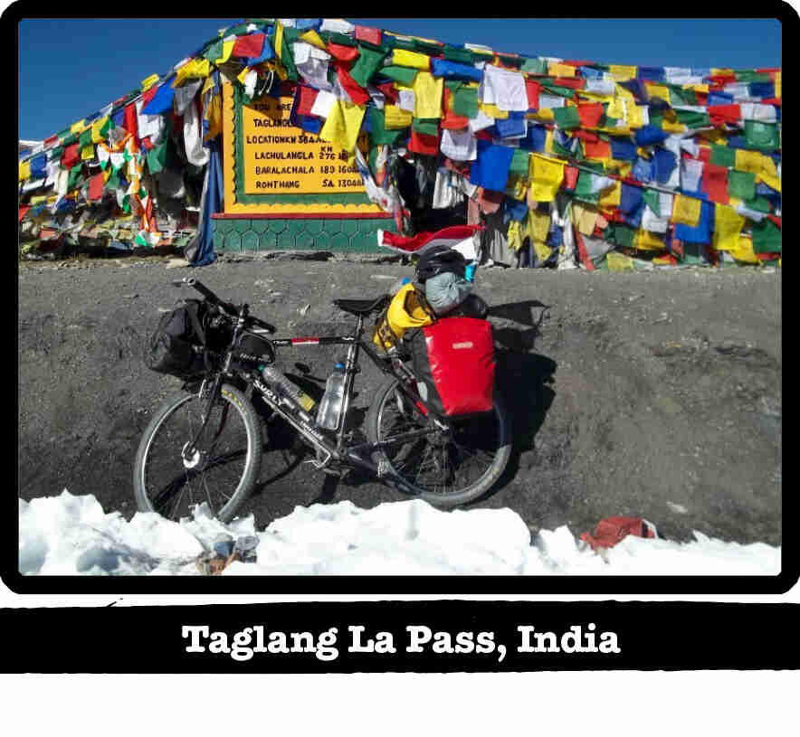 Left side view of a black Surly Long Haul Trucker bike, loaded with gear, on snow-Taglang La Pass, India tag below image