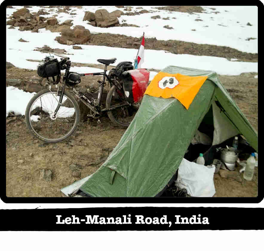 Surly Long Haul Trucker bike with gear, leaning on a rock behind a tent in the snowy mountains - Leh-Manali Road, India banner below image