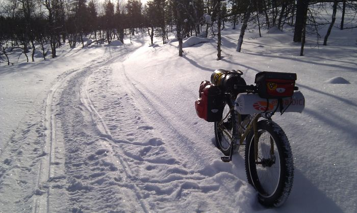 Surly Pugsley fat bike loaded with gear on a snowy trail in the woods on a sunny day
