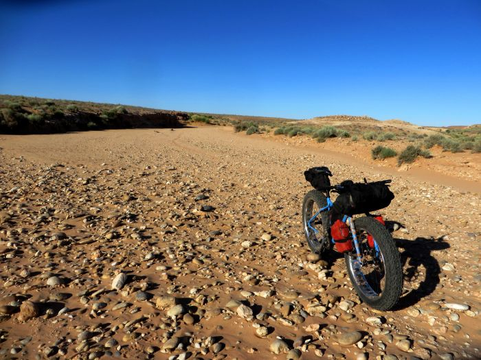 Angled view of left side of a Surly Ice Cream Truck fat bike with gear in a rocky sandy desert and blue skies