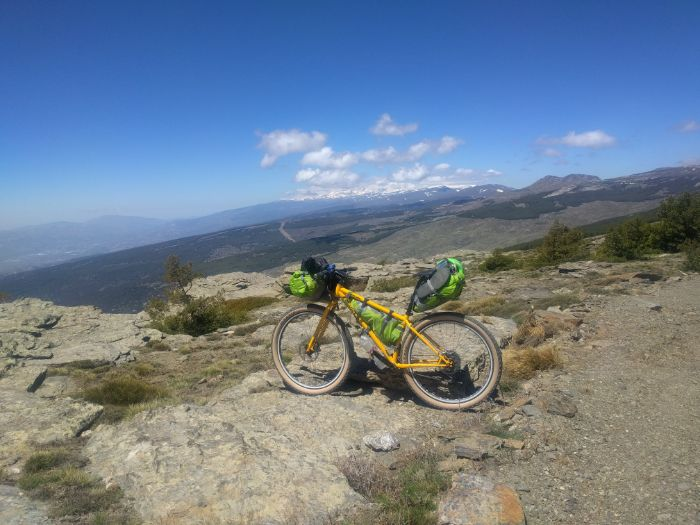 Left side view of a Surly Karate Monkey Bike with gear atop a rocky overlook into mountains and blue skies