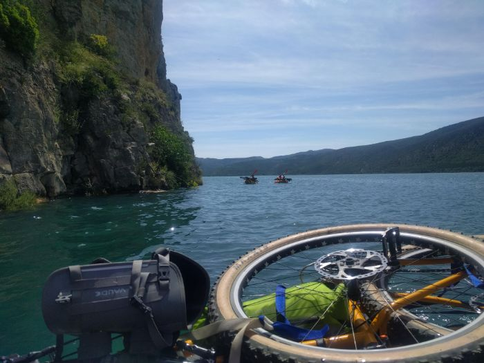 Front of a raft with gear and bike parts facing two rafters in the distance on a lake with a vertical cliff to the left