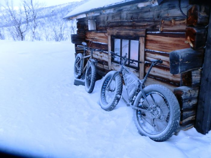 A Surly Moonlander and Pugsley fat bikes face each other leaning against a remote log cabin in deep snow