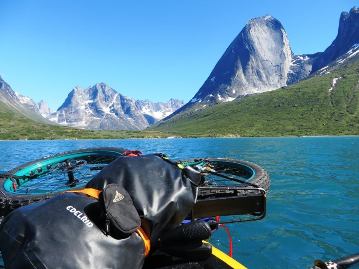 Surly Pugsley fat bike with green rims lying in a boat with gear on a mountain lake with clear blue skies