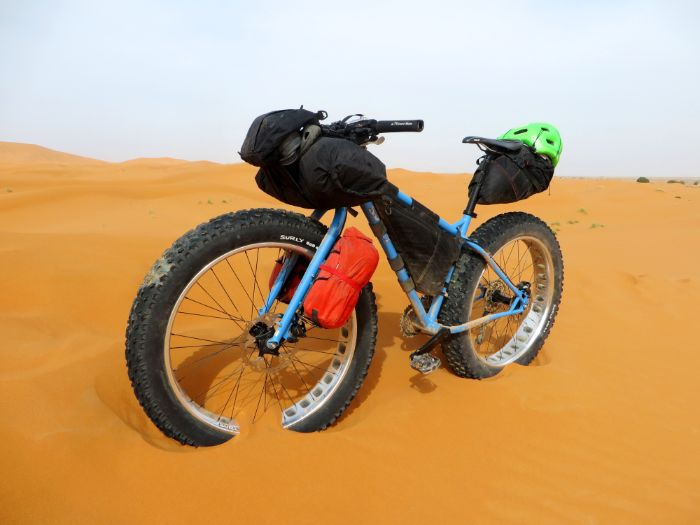 Left side view of Surly Ice Cream Truck fat bike with several gear bags standing in an orangish brown sand desert