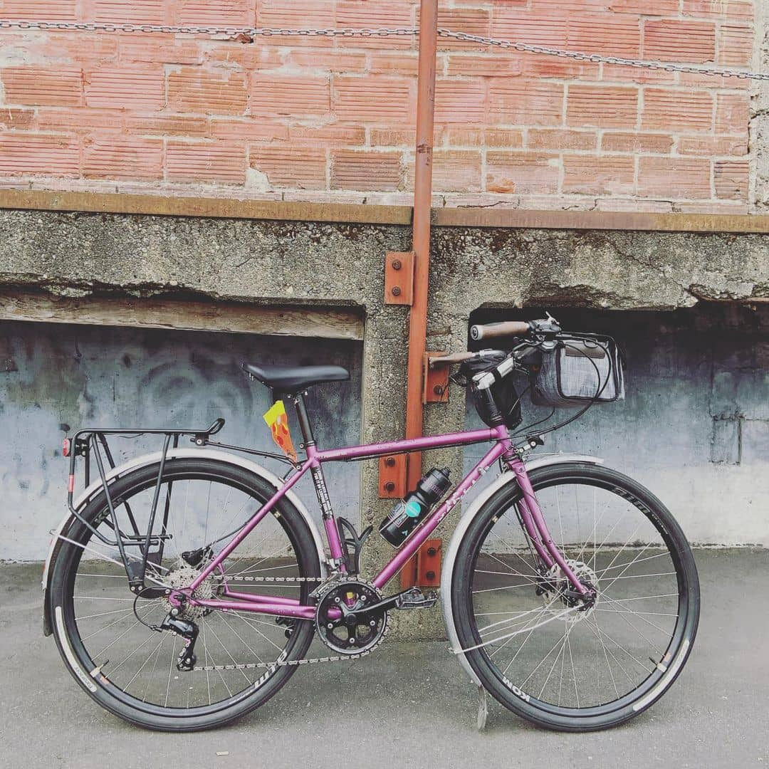 Right side of Surly Straggler bike colored in Glitter Dreams in front of a brick and concrete structure