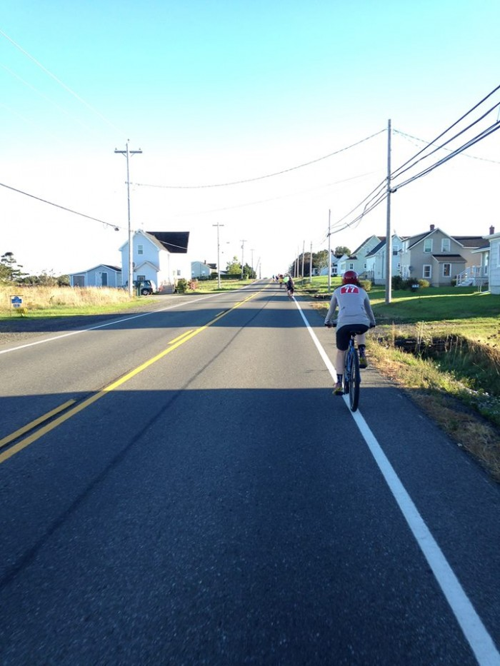 Rear view of cyclists riding down the side of a paved road with houses on both sides
