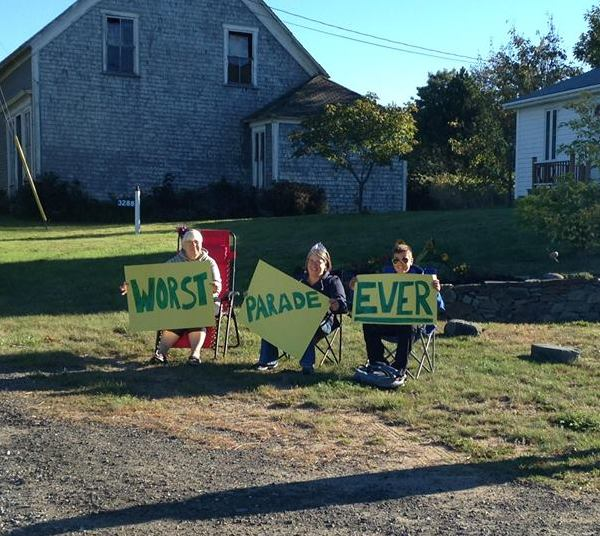 Front view of 3 people sitting in lawn chairs in front of a house, holding up signs that shows, Worst, Parade, Ever