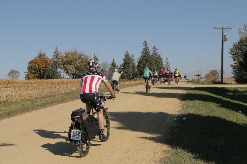 Rear view of a cyclist riding a Surly Big Dummy bike down a gravel road in the country, with a group of cyclists ahead