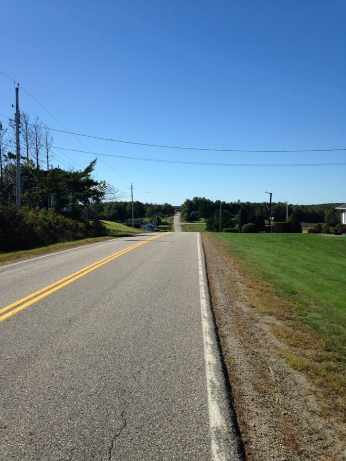 Straight away view of a paved roadway with a grass field to the right, and trees in the background