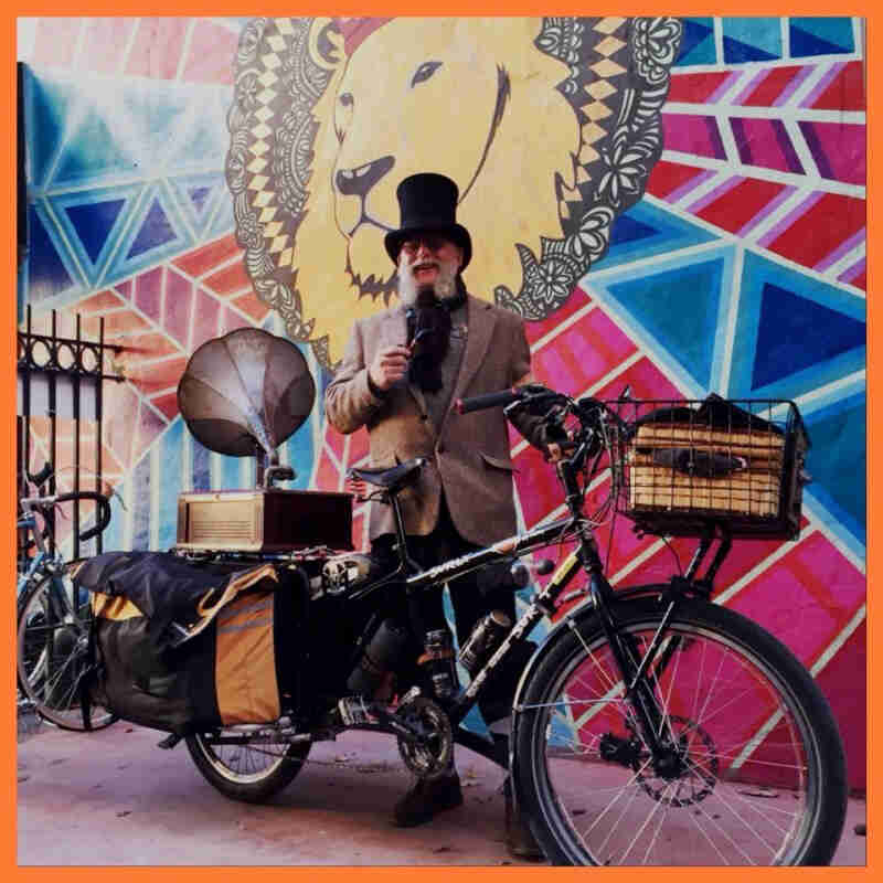 Right side view of a black Surly Big Dummy bike, with a person wearing a top hat holding a microphone standing behind