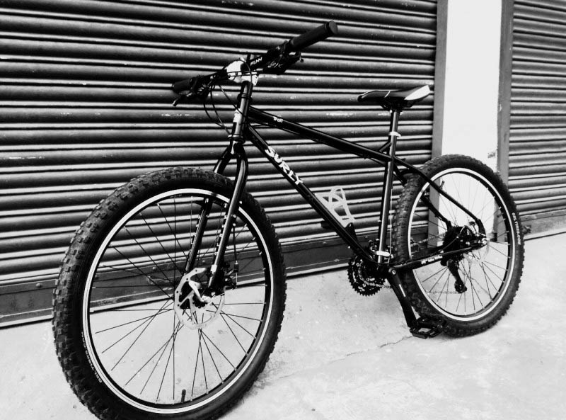 Left side view of a Surly Troll bike, black, on pavement, leaning on a steel garage door - black and white image