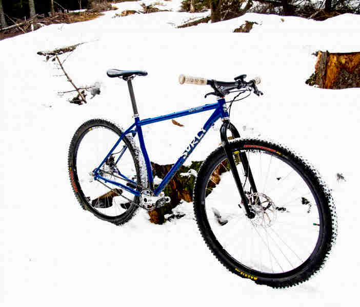 Right side view of a blue Surly bike, parked in a snow covered field, against a tree stump