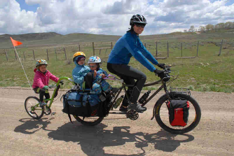 Right side view of a cyclist, riding a Surly Big Dummy bike with 3 children on back, on a gravel road in a rural area