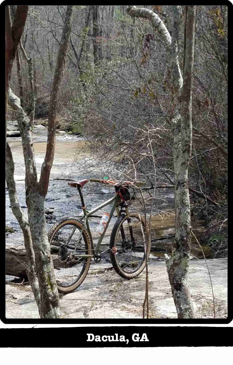 Right rear view of a Surly Karate Monkey bike, olive, at a flat rock on a river bank - Dacula, GA tag below image