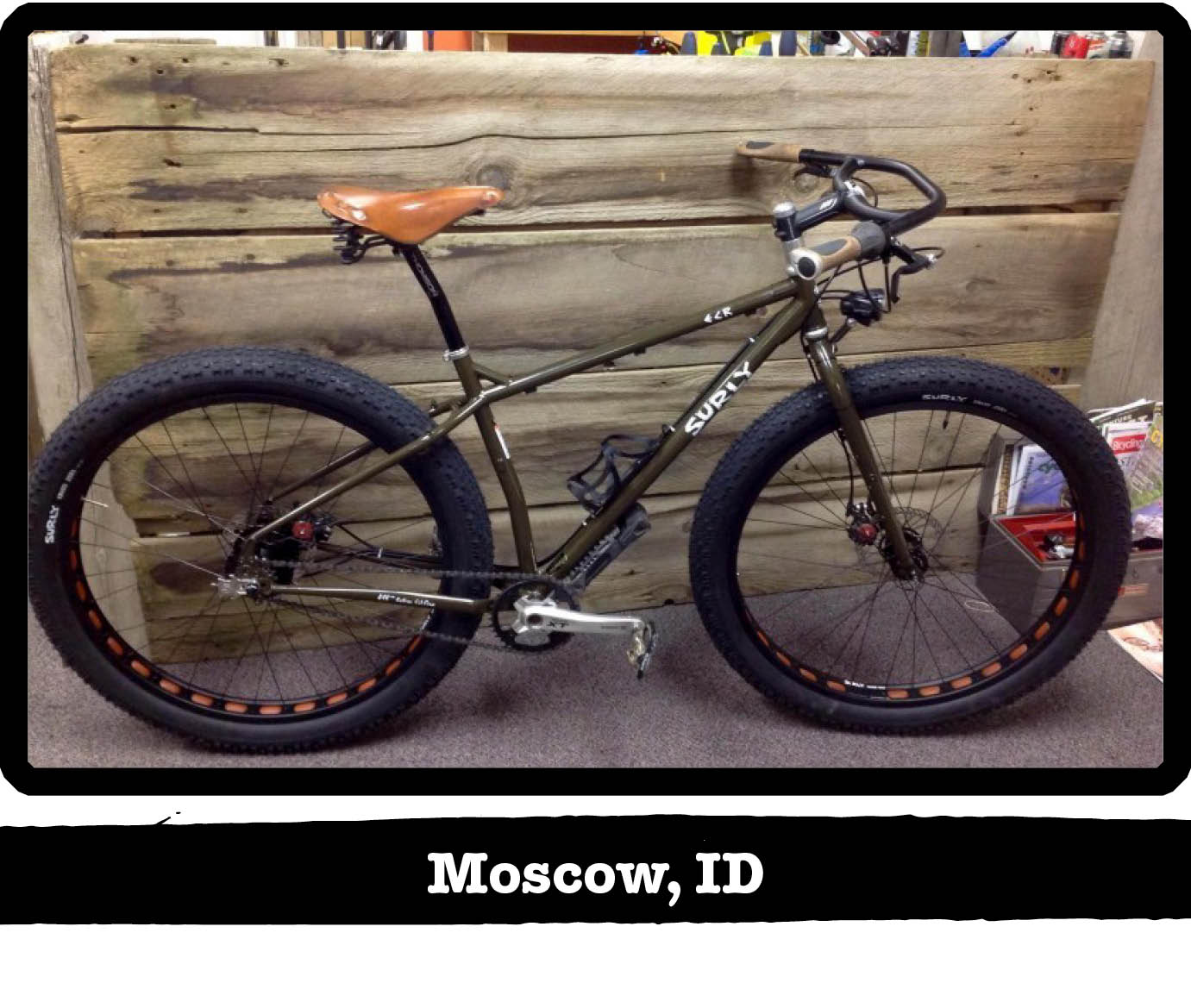 Right side view of a Surly ECR fat bike, olive drab, against a wood wall - Moscow, ID tag below image