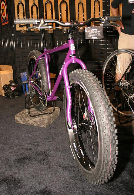 Front, right side view of a purple Surly Pugsley fat bike, in a carpeted room, and bike forks on the wall behind