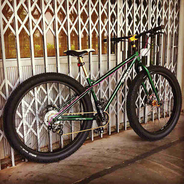 Right side view of a Surly Krampus bike, green, on a sidewalk, against a gate