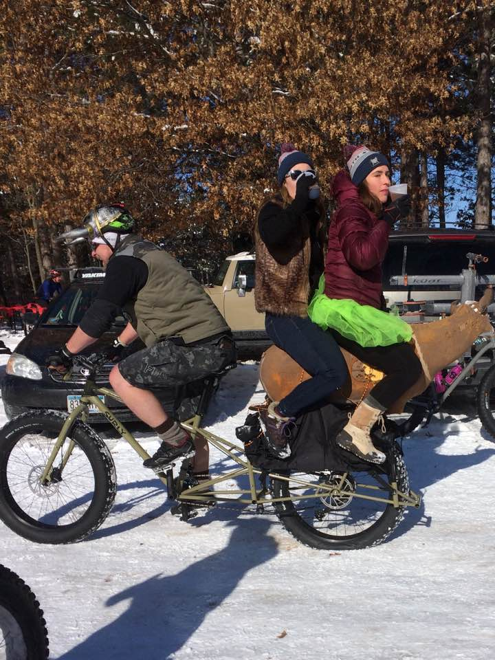 Left side view of a cyclist riding a a Surly Big Fat Dummy bike, with 2 people sitting on back, on a snowy covered lot