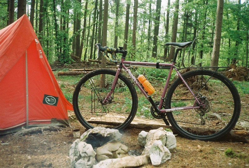 Left side view of a lavender color Surly Straggler bike, next to a red tent on the left, at a campsite in the forest