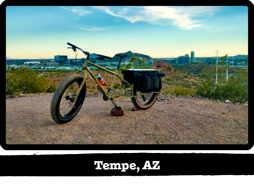 Left side view of a Surly Big Fat Dummy bike, green, on a gravel lot, with city behind - Tempe, AZ tag below image