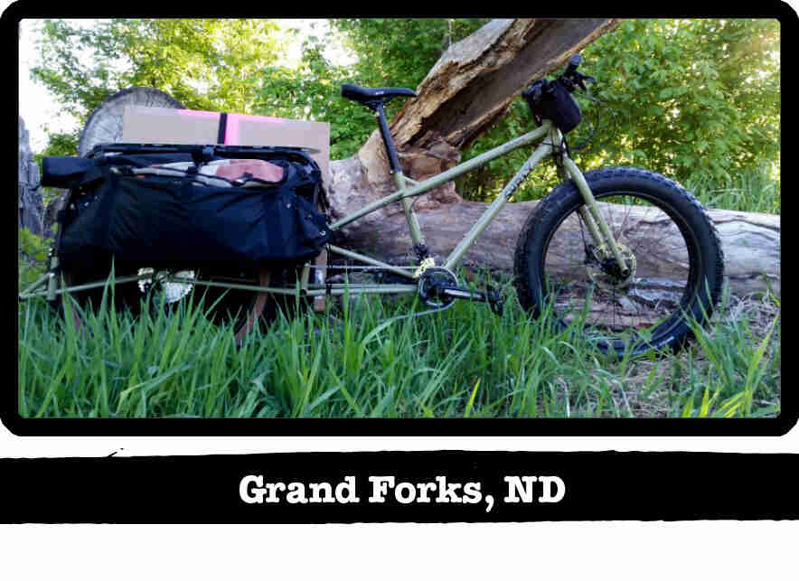 Right profile of a Surly Big Fat Dummy bike, olive, in tall grass against a downed tree - Grand Fork, ND tag below image