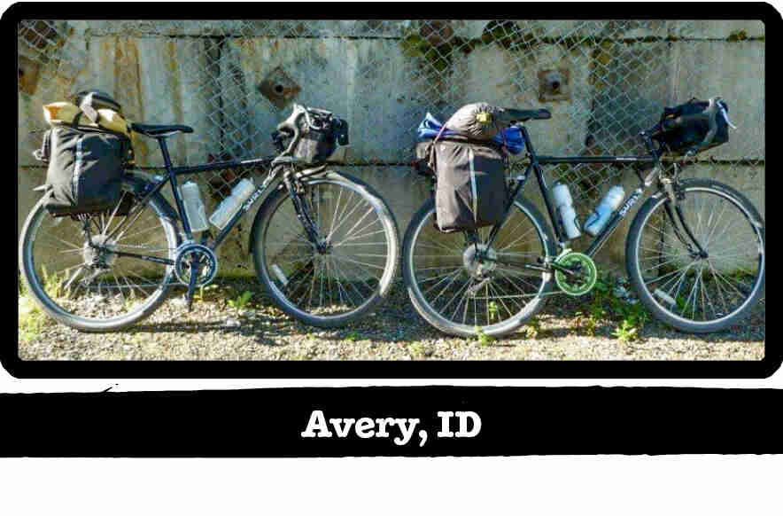 Right side view of 2 Surly bikes leaning on a chain link fence - Avery, ID tag below image