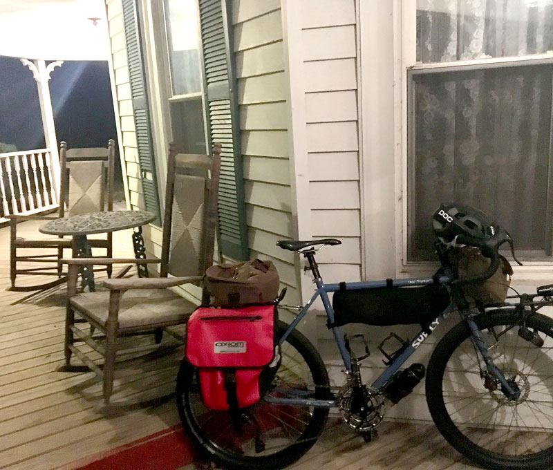 Right profile of a Surly bike, loaded with gear, on a porch against the window of a house with table and chairs behind