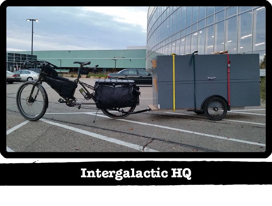 Left side view of a Surly Big Dummy bike with a trailer behind, on a parking lot - Intergalactic HQ tab below the image