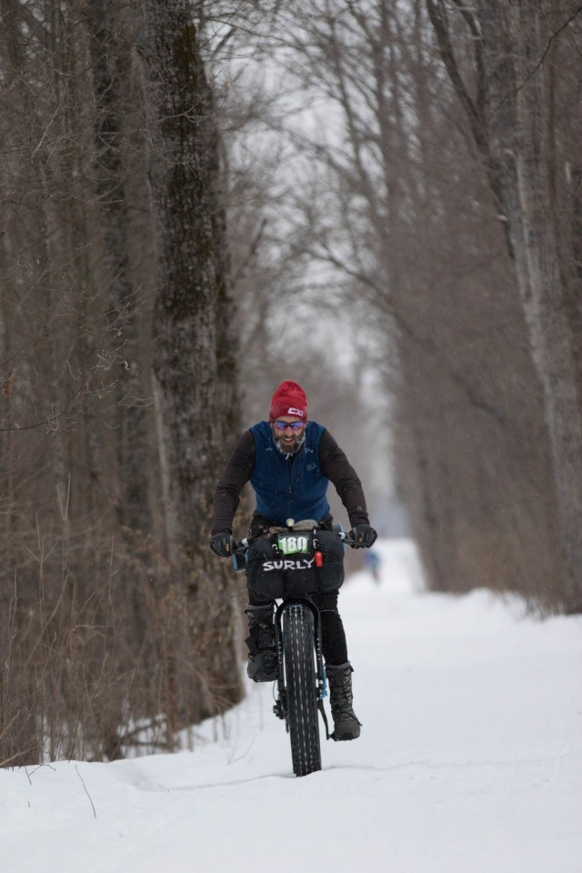 Front view of a cyclist riding a fat bike down a snow covered trail in the woods