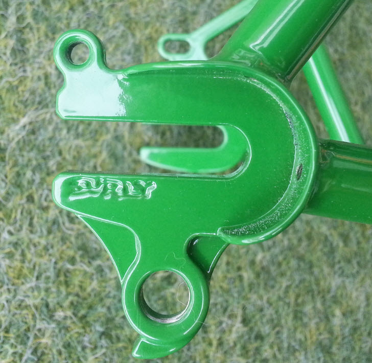Downward, close up, right side view of the dropout detail of a green Surly bike frame, with grass below it
