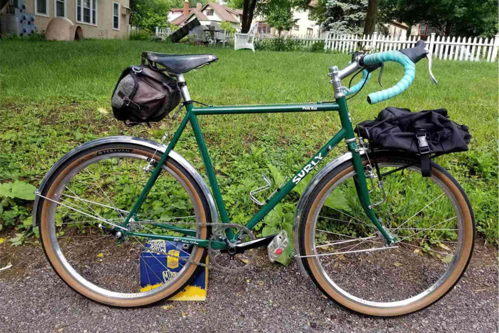 Right side view of a green Surly Pack Rat with gear packs on a sidewalk in front of a yard with a white picket fence