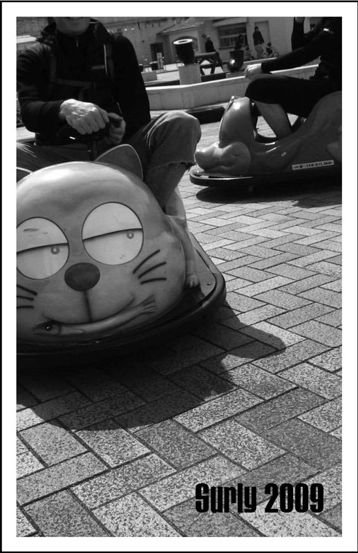 Surly Bikes - 2009 Catalog Cover - Black & White photo of a person driving a bumper car with a cat face on the front
