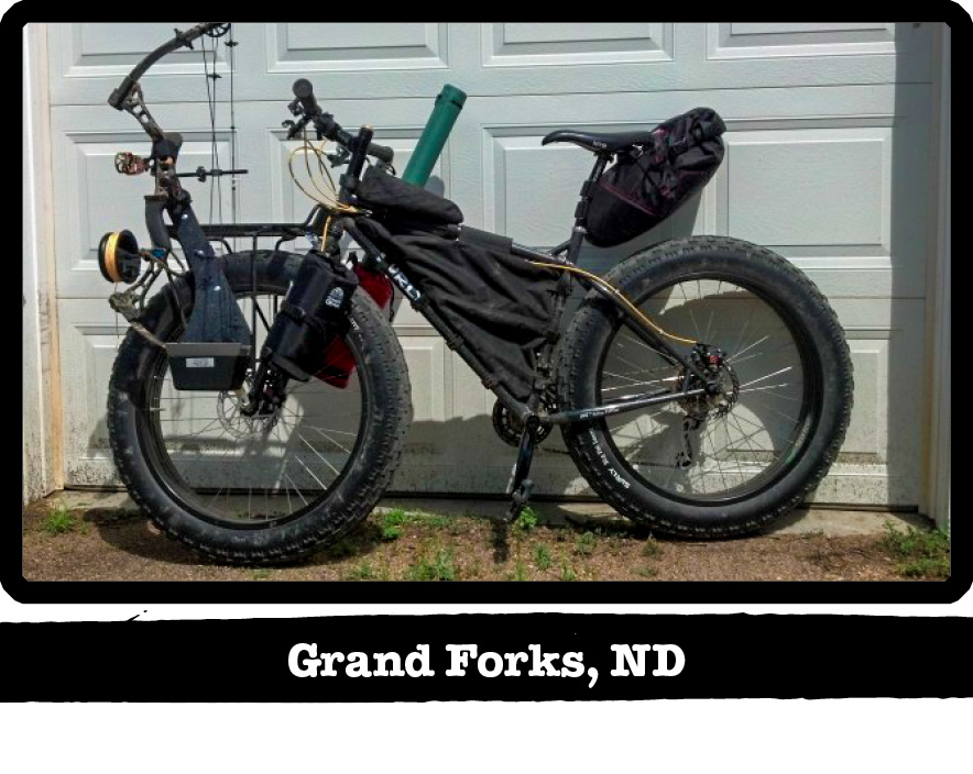 Left side view of a Surly fat bike, black, with a bow on front, against a garage door - Grand Forks, ND tag below image