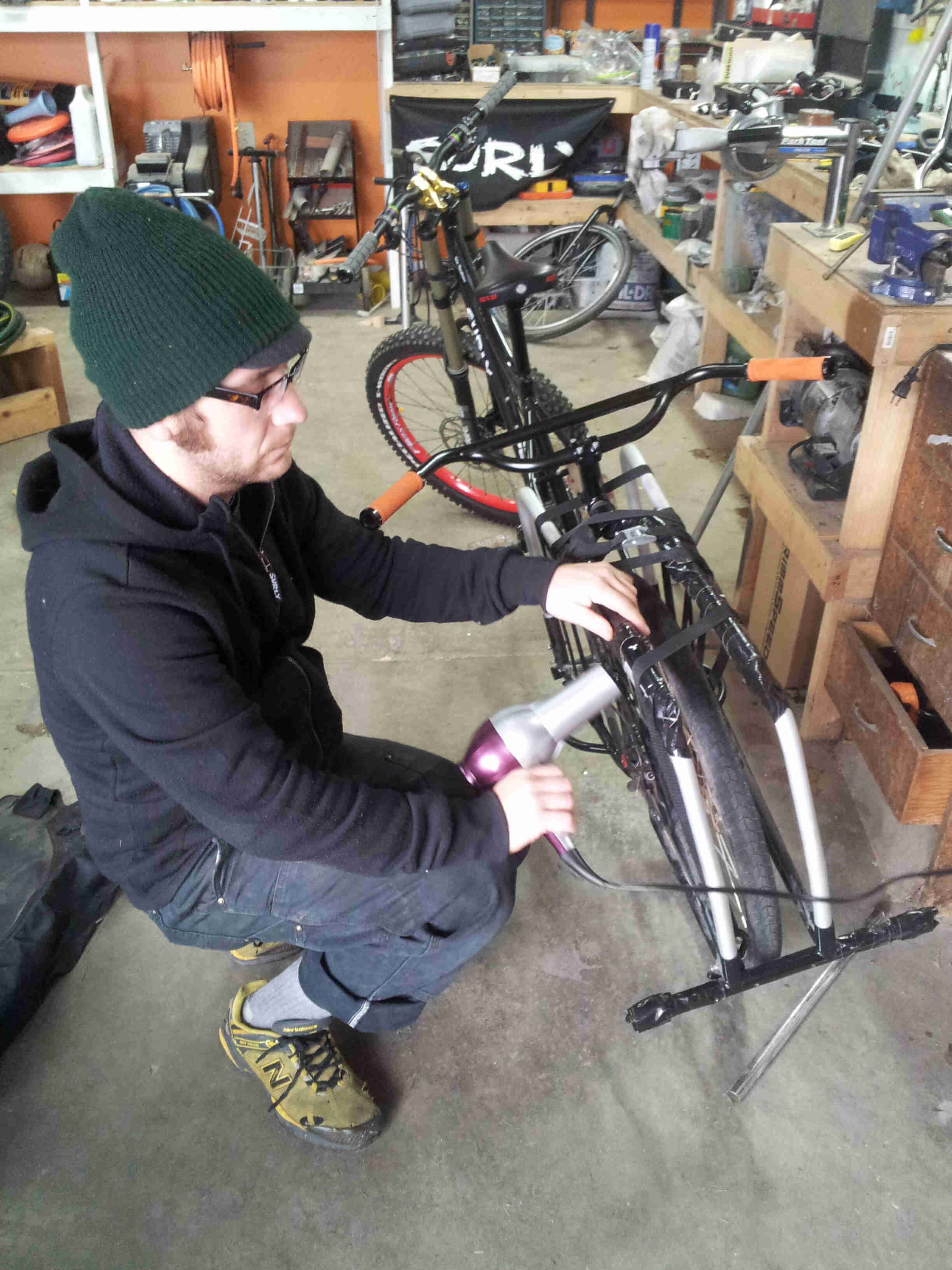 Rear view of a black Surly Big Dummy bike, with a person squatting down on the left side, inside of a workshop