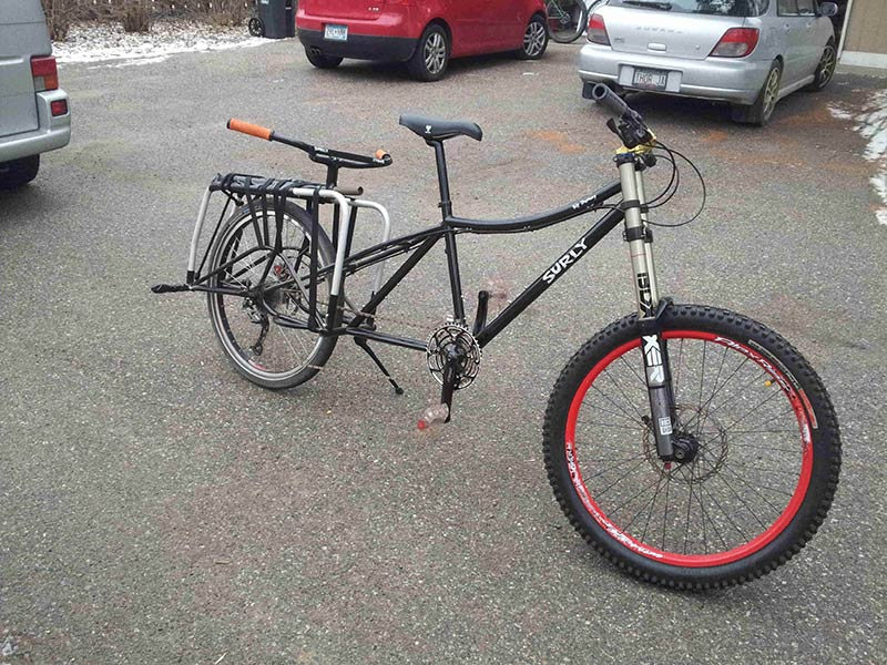 Right side view of a black Surly Big Dummy bike, standing on a paved parking lot, with vehicles behind it