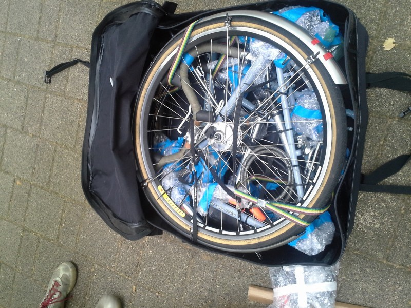 Downward view of a disassembled bike, packed inside of an open bike travel bag