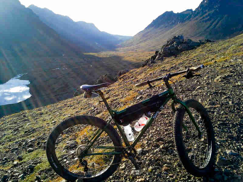 Right side view of a green Surly bike on a rocky hill in a mountain valley