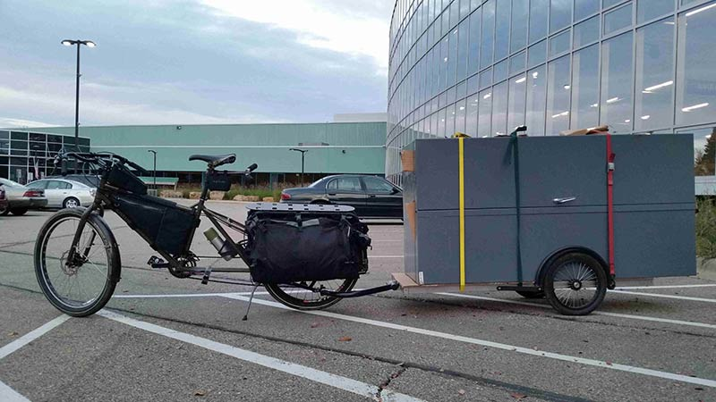 Left side view of a Surly Big Dummy bike, with a trailer loaded with cabinets, on a parking lot of an office complex