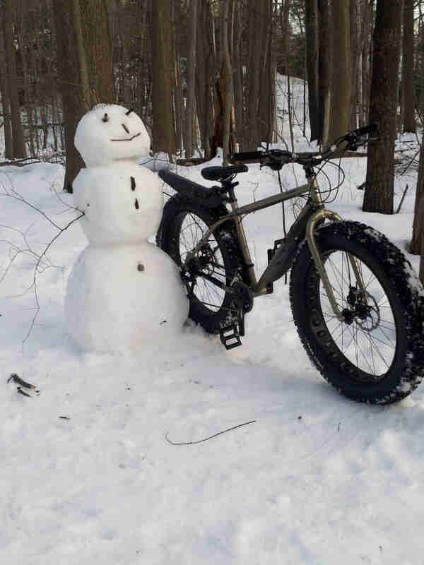 Front, right side view of a Surly fat bike, parked in the snow against a snowman, in the woods
