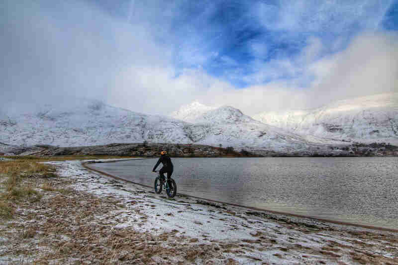 Rear view of a cyclist riding a fat bike along a frozen shore of a lake, with snow covered mountains in the background