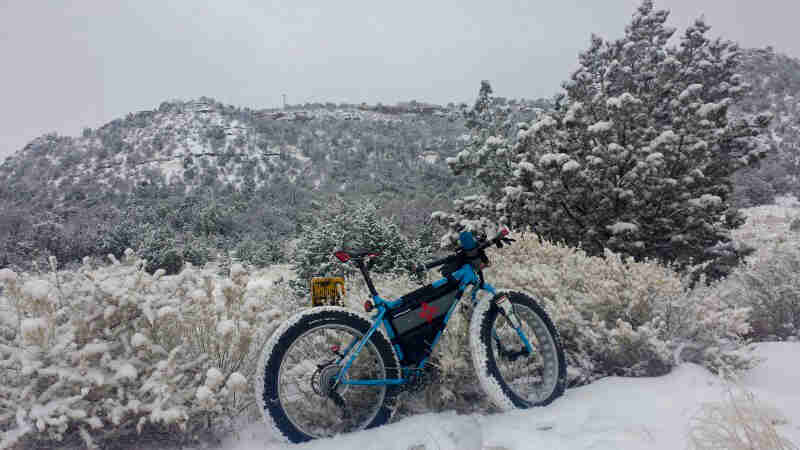 Right side view of a blue Surly fat bike, parked in snow, next to a grass field, with mountains in the background