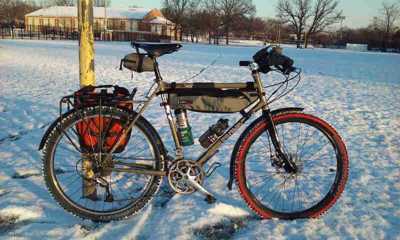 Right profile view of a Surly bike with gear, in a snowy field, with a building an tree in the background